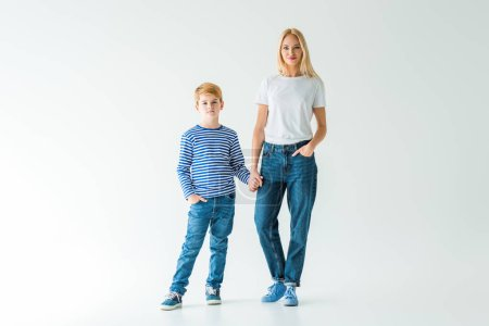 mother and son holding hands and looking at camera on white