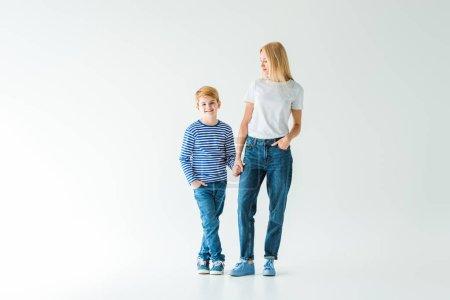 Photo pour Mère et fils souriant tenant la main et debout sur blanc - image libre de droit