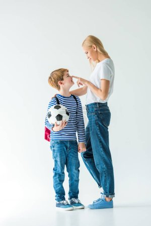 mother touching son nose, he holding football ball on white