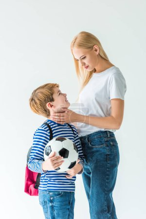 mother palming son, he holding football ball isolated on white