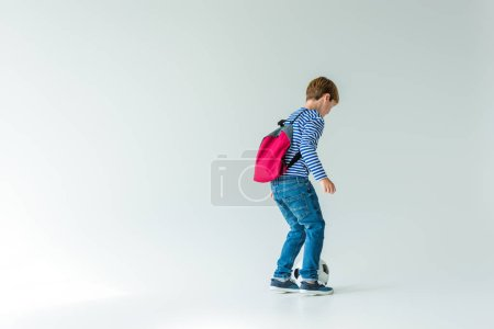 schoolboy with backpack playing with fotball ball on white