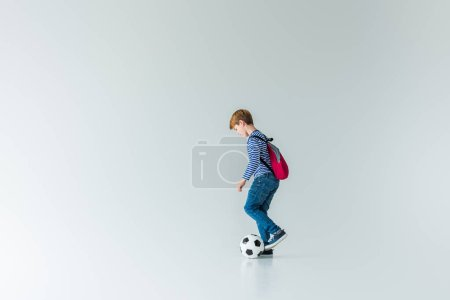 side view of schoolboy with backpack playing with fotball ball on white