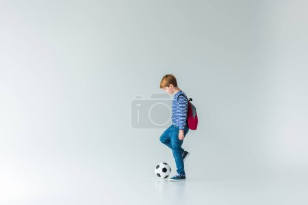 side view of adorable schoolboy with backpack playing with fotball ball on white