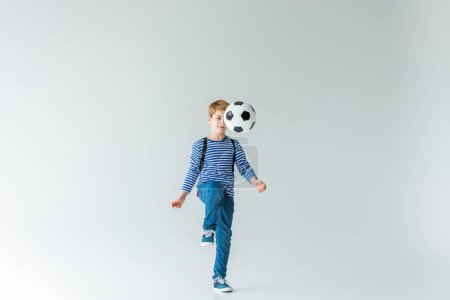 adorable schoolboy with backpack playing fotball on white