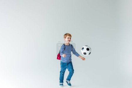 adorable schoolboy with backpack playing with fotball ball on white