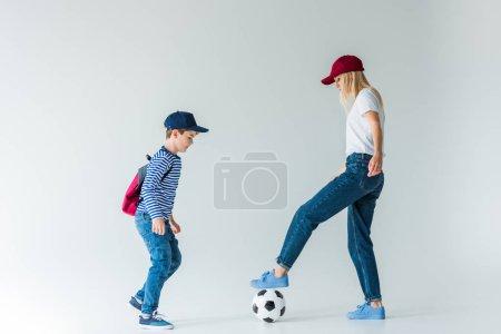 Photo pour Vue latérale de la mère en casquette et fils avec sac à dos jouant au football sur blanc - image libre de droit