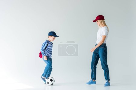 side view of mother and son with backpack playing with football ball on white