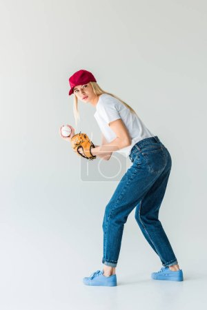 attractive baseball pitcher in red cap with baseball glove and ball isolated on white