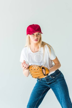 attractive baseball player in red cap holding baseball ball and glove isolated on white