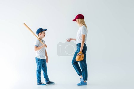 mother and son standing with baseball bat, glove, ball and looking at each other on white