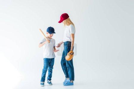 mother giving baseball ball to son on white