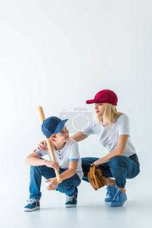 mother and son squatting with baseball bat and glove on white