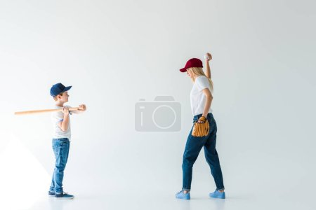 side view of mother pitching baseball ball to son with baseball bat isolated on white