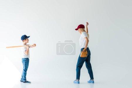 Photo pour Vue latérale de la mère lançant balle de baseball à son fils avec batte de baseball isolé sur blanc - image libre de droit