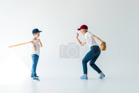 side view of mommy pitching baseball ball to son with bat isolated on white