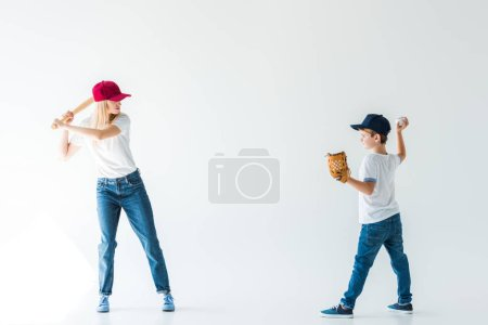 side view of son pitching baseball ball to mother with baseball bat isolated on white