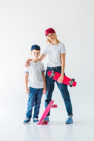 Photo pour Mère et fils en casquettes debout avec des patins et regardant la caméra sur blanc - image libre de droit