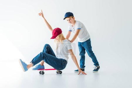 son pushing mother on skate on white, she showing one hand up