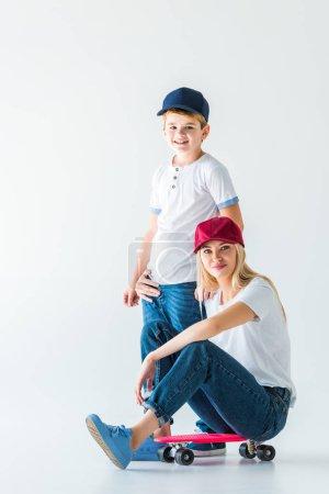 Photo pour Mère assis sur le patin, étreignant son fils et regardant la caméra sur blanc - image libre de droit