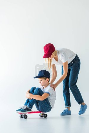 side view of mother in red cap pushing son on skate on white