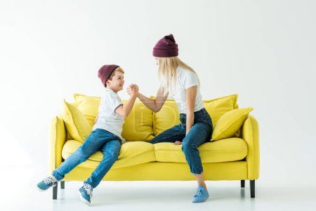 mother and son in burgundy hats arm wrestling on yellow sofa on white