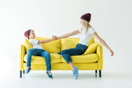 side view of mother and son in burgundy hats holding hands on yellow sofa on white