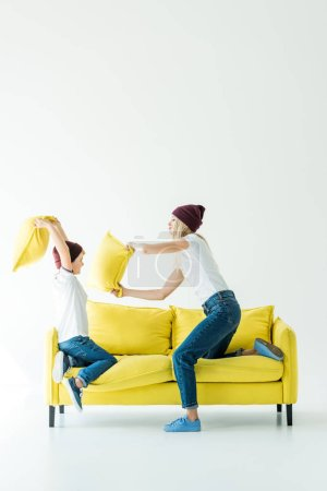 side view of mother and son having fun and fighting with pillows on yellow sofa on white