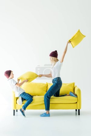 mother and son in burgundy hats having fun and fighting with cushions on yellow sofa on white