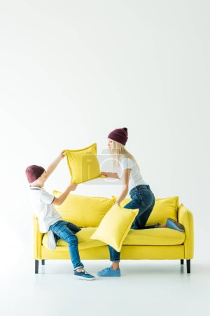 mother and son in burgundy hats having fun and fighting with pillows on yellow sofa on white