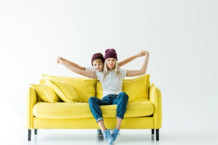 Photo for Mother and son in burgundy hats pretending flying on yellow sofa on white - Royalty Free Image