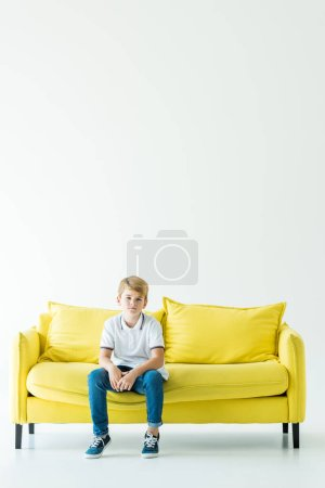 Photo for Adorable boy sitting on yellow sofa and looking at camera on white - Royalty Free Image