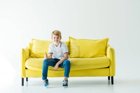 smiling adorable boy sitting on yellow sofa and showing thumb up on white