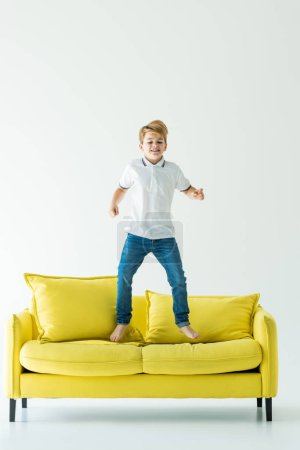 adorable boy having fun and jumping on yellow sofa on white