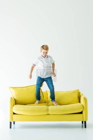 happy adorable boy jumping on yellow sofa on white