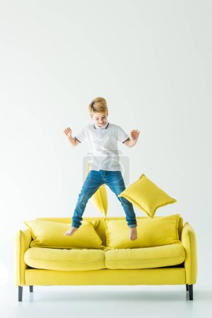 adorable boy jumping on yellow sofa on white