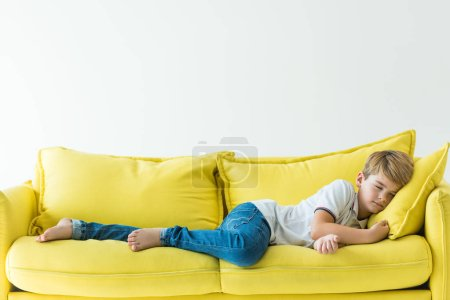 adorable boy sleeping on yellow sofa isolated on white