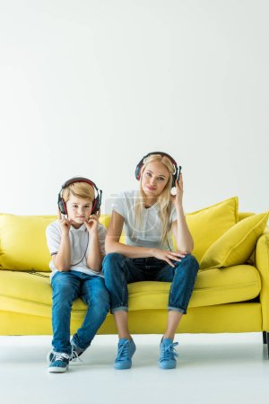 cheerful mother and son listening music with headphones on yellow sofa on white