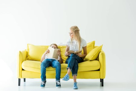 mother holding book and looking at son reading book on yellow sofa on white
