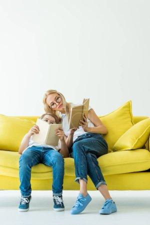 Foto de Madre e hijo, leer libros juntos en el sofá amarillo - Imagen libre de derechos