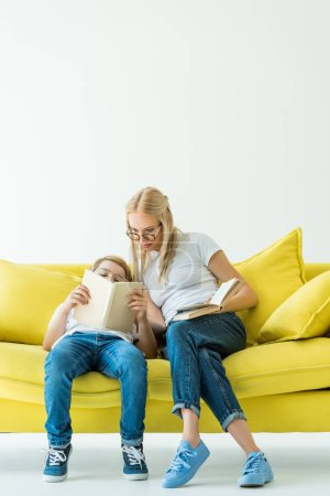mother and son reading book on yellow sofa on white