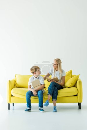 mother and son holding books and looking at each other on yellow sofa