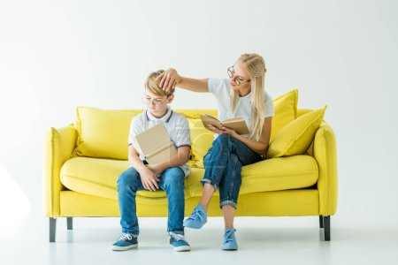 mother touching son hair while he reading book on yellow sofa
