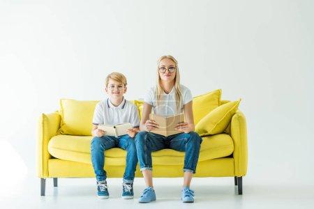 Photo pour Mère et fils dans des verres à maintenir les livres et en regardant la caméra sur le canapé jaune souriant - image libre de droit