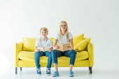 smiling mother and son in glasses holding books and looking at camera on yellow sofa