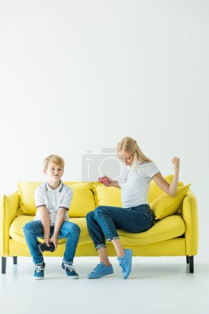 mother showing yes gesture after winning video game, son sitting upset on yellow sofa on white