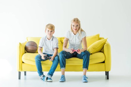 serious mother and son playing video game, basketball ball on yellow sofa