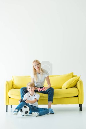 Photo for Happy mother and son playing video game on yellow sofa on white, football ball on floor - Royalty Free Image