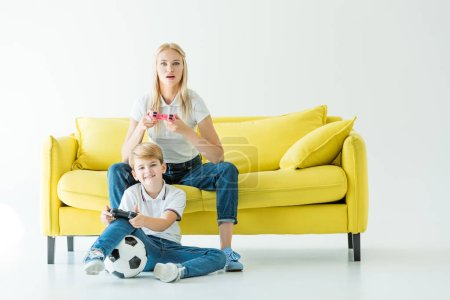 excited mother and son playing video game on yellow sofa on white, football ball on floor