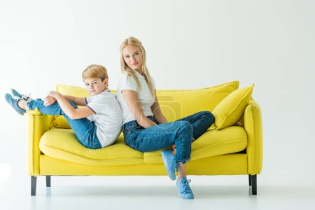 mother and son sitting back to back on yellow sofa on white