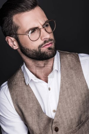portrait of handsome bearded man posing in eyeglasses, isolated on grey